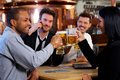 Young office workers toasting with beer at pub group of happy clinking looking each other smiling Royalty Free Stock Photo
