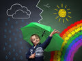 Young optimist a change in the weather child holding umbrella standing front of chalk drawing of changing from rain storm to sun Stock Image