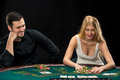 Young сouple playing poker, woman taking poker chips after winning