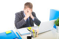 Young overworked and overwhelmed businessman covering his face suffering stress and headache Royalty Free Stock Photo