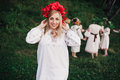 Young pagan slavic girl conduct ceremony on midsummer earth dayÑŽ girls in the ukrainian attire sitting against the backdrop of Royalty Free Stock Images