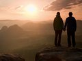 Young pair of hikers hand in hand on the peak of rock empires park and watch over the misty and foggy morning valley to Sun. Beaut Royalty Free Stock Photo