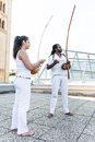 Young pair partners capoeira berimbau musical instrument in their hands Stock Photos