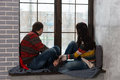 Young pair in warm knitted sweaters looking out the window while Royalty Free Stock Photo