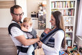 Young parents with children in sling and baby carrier Royalty Free Stock Photo