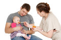 Young parents feed baby on a white background happy family Royalty Free Stock Image