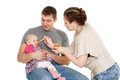 Young parents feed baby on a white background happy family Stock Image