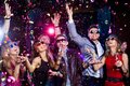 Young party cheerful people showered with confetti on a club Royalty Free Stock Photos