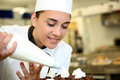 Young pastry cook at work putting whipped cream on cake Stock Photography