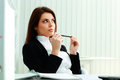 Young pensive businesswoman looking away at copyspace in office Stock Photo