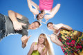 Young people across blue sky Royalty Free Stock Photo