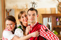 Young people in Bavarian Tracht in restaurant Royalty Free Stock Photography