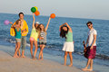 Young people enjoying a summer beach party dancing fun on the with guitar and balloons Royalty Free Stock Images