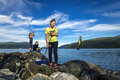 Young people are fishing on the rocks next to the fjord, Norway Royalty Free Stock Photo