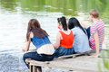 Young people friends sitting on the bridge teenage happy hugs at river summer water lake outdoors background Stock Images