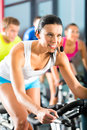 Young people group women men doing sport spinning gym fitness Royalty Free Stock Images