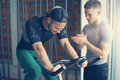 Young people in gym. Friends workout in gym and using smart phone. Royalty Free Stock Photo