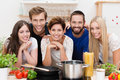 Young people in the kitchen preparing pasta group of diverse posing together while with an array of fresh ingredients and Royalty Free Stock Image
