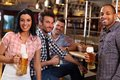 Young people in pub happy drinking beer smiling Stock Photography