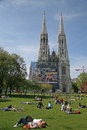 Young people relaxing on the grass of Sigmund Freud Park near The Votive Church (Votivkirche). VIENNA, AUSTRIA Royalty Free Stock Photo