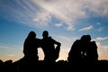 Young people silhouettes at sunset two girls and two boys Royalty Free Stock Photography