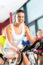 Young people spinning in the gym group of women and men doing sport for fitness Royalty Free Stock Images