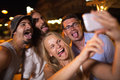 Young people taking crazy selfie with mobile friends funny faces making smart phone at night they fooling and putting out tongues Stock Photos