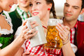 Young people traditional bavarian tracht restaurant pub beer steins Stock Image