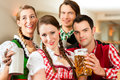 Young people traditional bavarian tracht restaurant pub beer steins Royalty Free Stock Photo