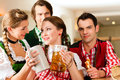 Young people traditional bavarian tracht restaurant pub beer steins Stock Photos