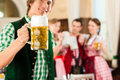 Young people in traditional bavarian tracht in restaurant or pub one man is standing with beer stein front the group the Stock Photography