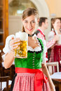 Young people in traditional bavarian tracht in restaurant or pub one woman is standing with beer stein front the group the Stock Photo