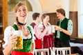 Young people in traditional bavarian tracht in restaurant or pub one woman is standing with beer stein front the group the Royalty Free Stock Photography