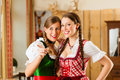 Young people in traditional bavarian tracht in restaurant or pub two women Stock Image