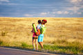 Young people traveling hitchhiking summer field two Stock Photo