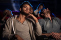 Young people watching a boring film at the cinema Royalty Free Stock Photo