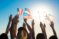 Young people waving American flags at sunset. Royalty Free Stock Photo