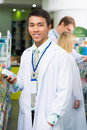 Young pharmacist vertical portrait of a male with a box of treatment standing in the drug store on the foreground Royalty Free Stock Photography
