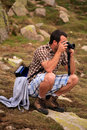 Young photographer shoot photos in high rocky mountain Stock Photography