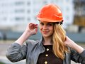 The young pleasant smiling girl with long hair costs against building under construction Stock Images