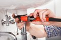 Young plumber fixing a sink in bathroom Royalty Free Stock Photo