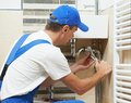 Young plumber man worker working with spanner at sanitary washbasin installation system Stock Photos