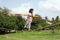 A young poor trapeze girl balances on her rope and does her tricks to make a living in india Stock Photo