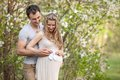 Young pregnant couple outdoors in spring blossom Royalty Free Stock Photos