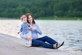 Young pregnant mother and her baby daughter on shore of river attractive adorable curly Royalty Free Stock Image