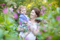 Young pregnant mother holding her baby daughter in a garden on sunset Stock Photo