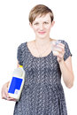 Young pregnant woman drinking fresh milk a glass of while holding a plastic bottle with a blank blue label benefit of increased Royalty Free Stock Image