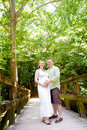 Young pregnant woman and handsome man happy couple expecting a baby standing on a wooden bridge Stock Images