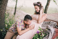 Young pregnant woman with her husband sitting near lake women in a pink dress on a berth kissing Royalty Free Stock Photo
