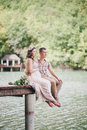 Young pregnant woman with her husband sitting near lake women in a pink dress kissing Royalty Free Stock Photos